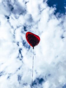 A red balloon in the shape of a heart against the white clouds